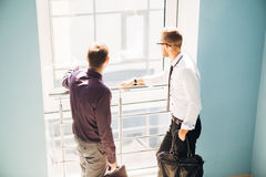 Two men talking in the lobby of the office. Two men talking in the lobby of the modern office Stock Photo
