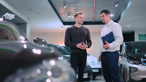 Two men are talking near the electric car. Shooting in front of the car. The car at the foreground are blurred. The manager and young man are talking near the stock footage