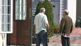 Two men talking outside a store. A view or scene from around town stock footage
