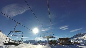 Two men are talking sitting on the chair ski lift. Slow motion: Two men are going up by chair ski lift on sunny day, Tignes, France stock footage