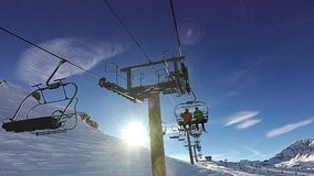Two men are talking sitting on the chair ski lift. Slow motion: Two men are going up by chair ski lift on sunny day, Tignes, France stock video footage