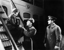 Two men talking to a young woman sitting on the ship's step Stock Photos