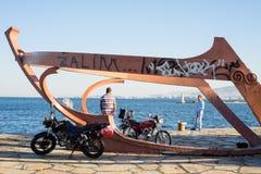 Two Men Talking at Waterfront beside Sculpture of Ship Skeleton Stock Photos