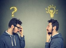 Two men thinking one has a question another solution with light bulb above head Royalty Free Stock Photo