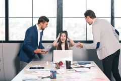 Two men scream at a girl who clings to her head and cries. Inside the office. Two men threateningly scream at a young girl, and frantically clinging to her head Stock Images