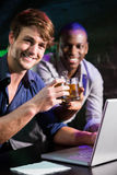 Two men toasting their whiskey glasses at bar counter while using laptop Royalty Free Stock Image