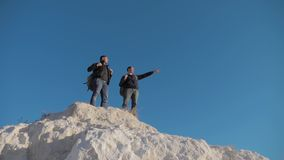 Two men tourists hiking adventure climbers climb the mountain . slow motion video. hiker walking on top win victory the. Two men tourists hiking adventure stock footage