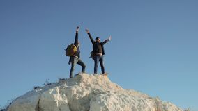 Two men tourists hiking adventure climbers climb the mountain success hand to hand freedom up. slow motion video. hiker. Two men tourists hiking adventure stock video footage