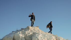 Two men tourists hiking adventure climbers lifestyle climb the mountain . slow motion video. hiker walking goes on. Nature on hill white rock. extreme outdoor stock footage