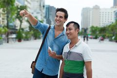 Two men tourists smile point finger sightseeing Stock Photography