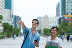 Two men tourists smile point finger sightseeing Royalty Free Stock Photo