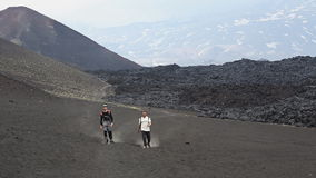 Two men tourists walk down the volcano after climbing to top. TOLBACHIK VOLCANO, KAMCHATKA PENINSULA, RUSSIA - JUNE 24, 2016: Hiking on Kamchatka - two men stock video