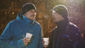 Two men in the evening in winter in the street talking and drinking coffee. It`s snowing.