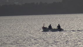 Two Men Travel in a Small Boat. Long shot of two men who travel in a small boat during nightfall stock video footage
