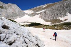 Two men trekking mountains. Two male hikers walking in snow among Pirin mountain range in Bulgaria Royalty Free Stock Photos