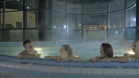 Two men and two girls are swimming in the pool after the sauna stock video