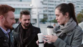 Two men and two woman spend time in the city. A beautiful girl brings coffee to her friends. Slow mo, steadicam shot stock footage