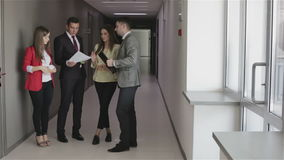 Two men and two women in fashionable clothes discuss work. Business team concept. Two men and two women in fashionable clothes discuss work. People standing in stock video