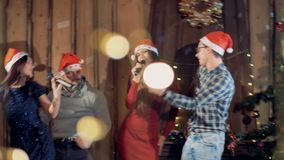 Four people dance and sing at Christmas time. Two men and two women sing and dance at Christmas eve stock video