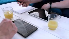 Men work with tablets in a cafe. Two men are typing on a tablet in a cafe. View from above stock video footage