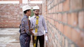 Two men in uniform measuring wall with instrument on site. Side view of two men using builder`s level on brick wall while working on construction stock video footage
