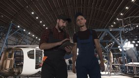 Two men discussing in aircraft hangar. Two men in uniform walking in aircraft hangar and discussing over digital tablet stock video footage