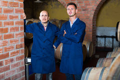 Two men in uniforms standing in cellar with wine woods Stock Image