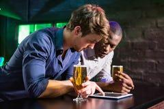 Two men using digital table while having beer at bar counter Stock Photos