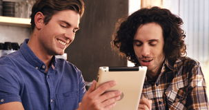 Two men using digital tablet in café. Two men sitting at a table and using digital tablet in café 4k stock footage