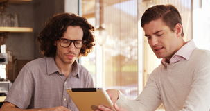 Two men using digital tablet in cafe. Two men using digital tablet while having a meeting in cafe 4k stock footage