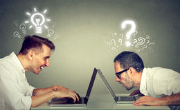 Two men using laptop computer one educated has bright ideas the other ignorant has questions. Side profile two men using laptop computer one educated has bright Royalty Free Stock Photo