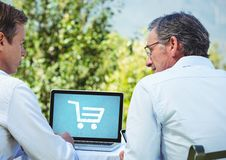 Two men using Laptop with Shopping trolley icon Stock Images