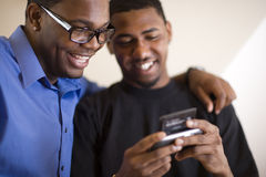 Two men using PDA. African American young men text messaging on PDA Stock Photos