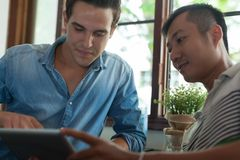 Two Men Using Tablet, Asian Mix Race Friends Guys Royalty Free Stock Images