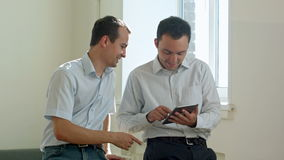 Two Men Using Tablet Computer Internet, Financial adviser showing terms of contract on tablet stock video footage