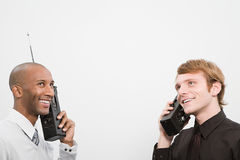 Two men using walkie talkies stock image
