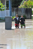 Two men wade through flooded street Stock Photo