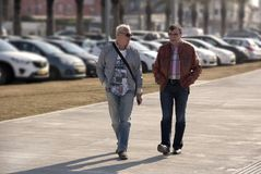 Two men walk around the city and communicate. Two men walk arTwo men walk around the city and have a dialogue with each other on the blurred backgroundound the royalty free stock image