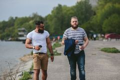 Two men walk and drink coffee. Two  men with a cups of coffee looking at the beach Stock Photo