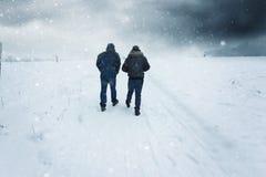 Two men walking along the snowy footpath in the stormy weather. Two men walking along the snowy footpath stock photo