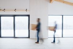 Two men walking with cardboard boxes when furnishing new house. Motion blur. Unrecognizable men walking with cardboard boxes when furnishing new house royalty free stock photo