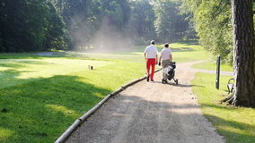 Two men walking down a sand path with to the next hole stock footage