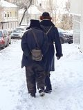 Two men walking down the street in an old revolutionary clothing, retro style. Winter, Russia royalty free stock photography