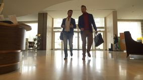 Two men walking in lobby hotel on background revolving door low angle view. Two men walking in lobby hotel on background revolving door in modern business center stock footage