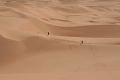 Two men walking in the middle of Sahara desert Royalty Free Stock Image