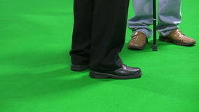 Two men with walking sticks on green. Legs of two men with walking sticks isolated standing on green carpet background stock video footage