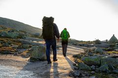 Two hikers seen from behind, walking on the track to Trolltunga, in a beautiful landscape in Odda, Norway Stock Images