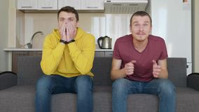 Two men watch a football match on TV and support different teams
