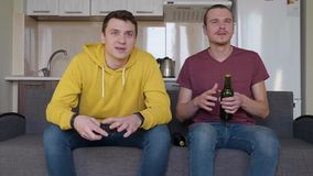 Two men watching a football match and open a bottle of beer. The guy brings a drink, sitting next to his friend and carefully watches TV. A kitchen on the stock footage