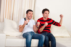 Two men watching tv soccer. Two excited men sitting on couch and watching favorite team soccer with goal Royalty Free Stock Photos